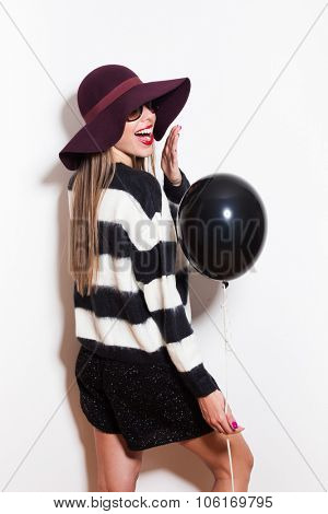 young woman with hat sunglasses and sweater laughing and hold black balloon, studio white