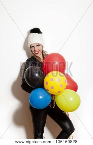 smiling young woman wearing black leather jacket, pants and white wool cap, hold balloons, studio white