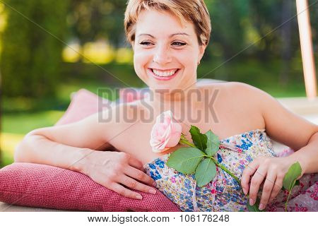 Young smiling woman with rose