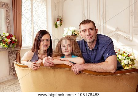 Nice family of three looking at camera and smiling
