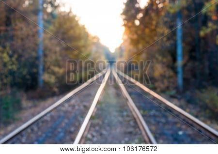 Blurred railway in the autumn forest. Travel background