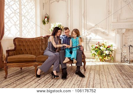 Mother and father reading book to their daughter
