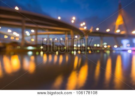 Blurred bokeh lights of water reflection suspension bridge and highway intersection at night