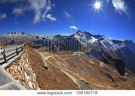 Sunny day in early autumn Austrian Alps. Excursion to the picturesque panoramic way Grossgloknershtrasse. Great highway winds between hillsides yellowed
