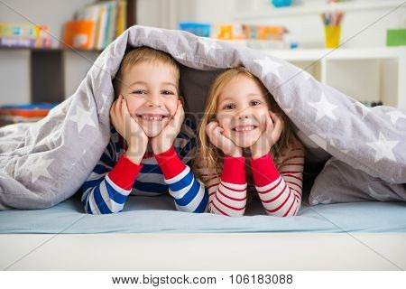 Two Happy Children Lying Under Blanket