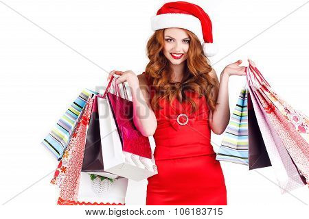 Studio portrait of redhead girl with colored bags for shopping