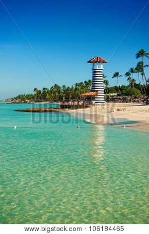 Striped Lighthouse On Sandy Shore With Palm Trees. Clear Water Of The Caribbean Sea.