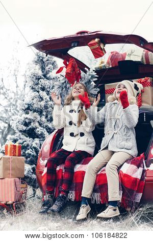Holiday preparations. Pre teen children enjoy many Christmas presents in car trunk. Cold winter, snow weather.