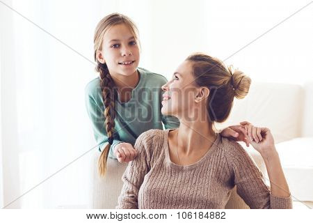 Mom with her pre teen daughter hugging, positive feelings, good relations.