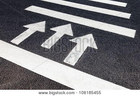 Urban Pedestrian Crosswalk With White Marking Lines And Direction Of Motion On Asphalt