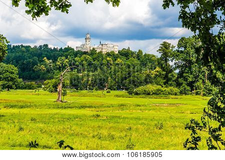 Picturesque view of beautiful Hluboka castle with cloudy sky and forest-Hluboka nad Vltavou Czech Republic Europe