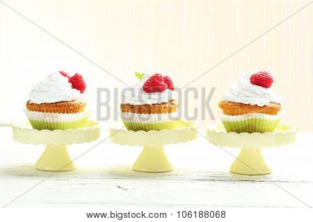 Raspberry Cupcakes On Cake Stand On White Wooden Background