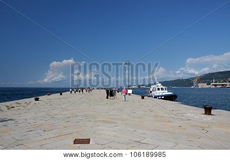 Tourists Walking On Molo Audace In Trieste, Italy On Summer Day.