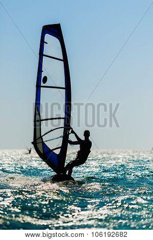 windsurfer silhouette against sun