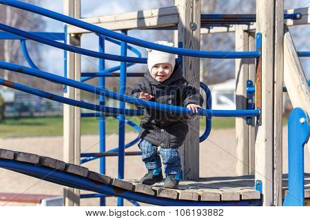 Little Child Walks Along The Boards On The Playground