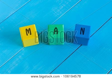 Man - sign on color wooden cubes with light blue wood background.
