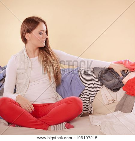 Woman Sitting On Sofa In Messy Room At Home.