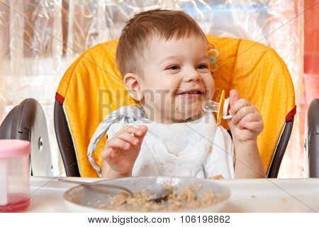 Happy Baby Boy Holding Pacifier And Smiles At Breakfast