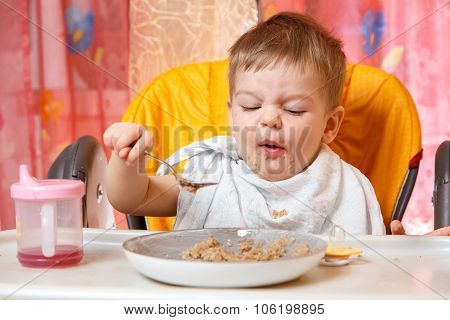 Funny  Baby With Grimace Holds  Spoon With Buckwheat Cereal