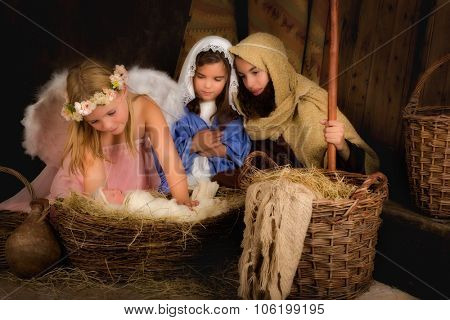Little 7 year old angel visiting a nativity scene reenacted - the baby is a doll