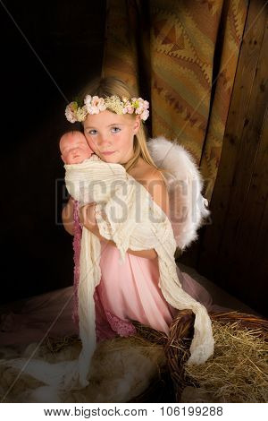 Pink little girl playing an angel in a Christmas nativity scene - the baby is a doll