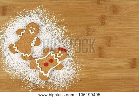 Christmas gingerbread people with powdered sugar on wood