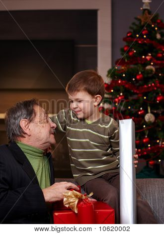 Young Boy Getting Christmas Present From Grandfather