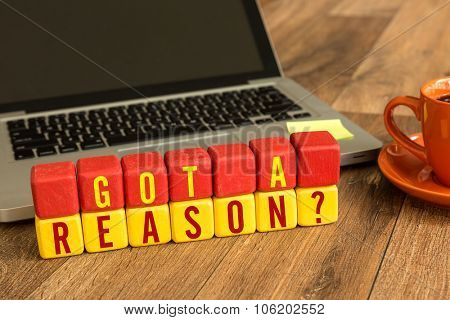 Got a Reason? written on a wooden cube in front of a laptop