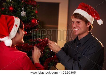 glückliches paar ergänzenden Weihnachtsbaum