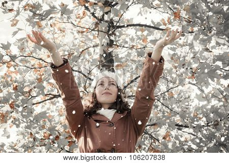Happy young woman and falling snow with tree in background