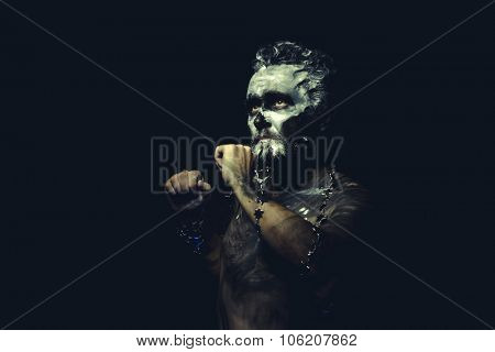 wild man with white painted face and full body black paint