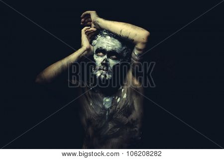Ethnic, wild man with white painted face and full body black paint