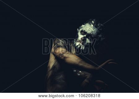 Cave, wild man with white painted face and full body black paint