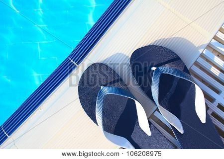 Summer Vacation Concept. Flipflops At The Edge Of The Swimming Pool