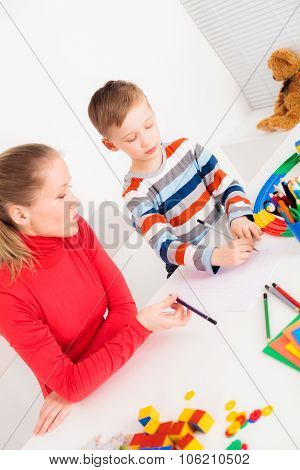 Mother and son drawing at desk