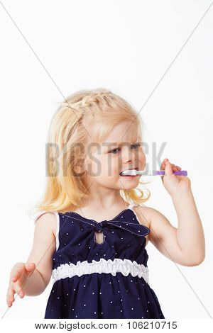 Beautiful blonde haired girl with toothbrush in her hand