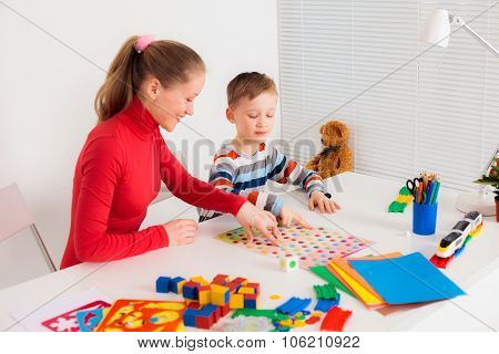 Mother playing with her son at desk