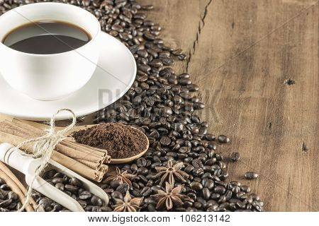 Coffee On The Cup With Coffee Beans And Cinnamon Sticks On Wood Background, Soft Toning, Selective F