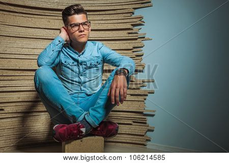handsome young man sitting in studio with legs crossed while wearing glasses