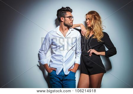 man with hands in pockets looking at woman dressed in black who rests her arm on his shoulder