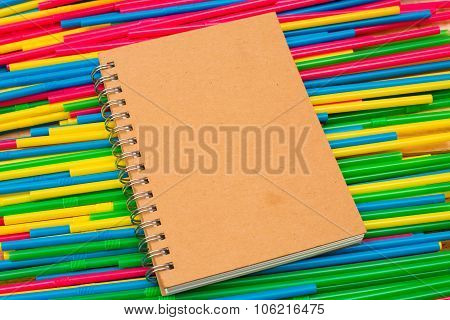 Notebook On Top Colorful Straw Tubes Closeup. Abstract Texture And Background.on Wooden Table