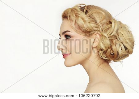 Profile portrait of young beautiful blonde woman with stylish prom hairdo