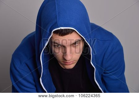 Portrait Of A Confident Young Man Wearing Blue Hooded Sweatshirt