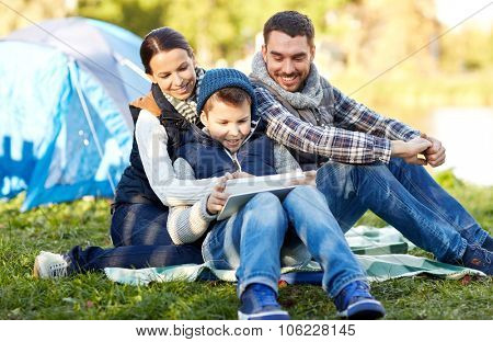 camping, tourism, hike, technology and people concept - happy family with tablet pc computer and tent at camp site