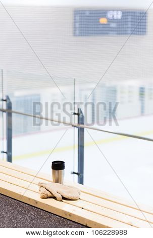 hot drink, winter and leisure concept - close up of thermos cup and sheepskin mittens on bench at ice rink arena