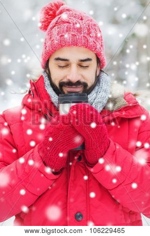 season, christmas, drinks and people concept - happy smiling young man with thermo cup drinking hot tea in winter forest