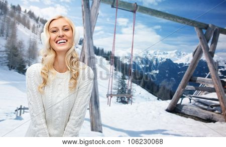 winter, vacation, christmas and people concept - smiling young woman in earmuffs and sweater over snowy mountains and wooden swing background