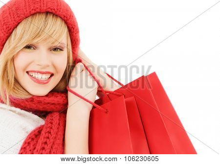 happiness, winter holidays, christmas and people concept - smiling young woman in hat and scarf with red shopping bags over white background