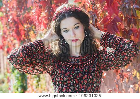 Portrait Of Melancholy Autumn Girl With Autumn Wreath At Red Floral Background Of Grape Woodbine