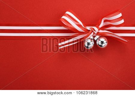 Ribbon bow with jingle bell on paper textured background